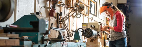Photo of Katie Stofel using wood-working equipment