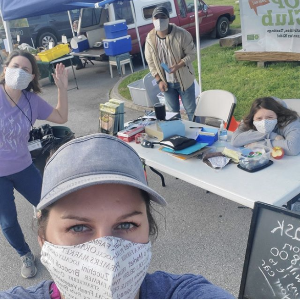 people in face masks at farmers' market