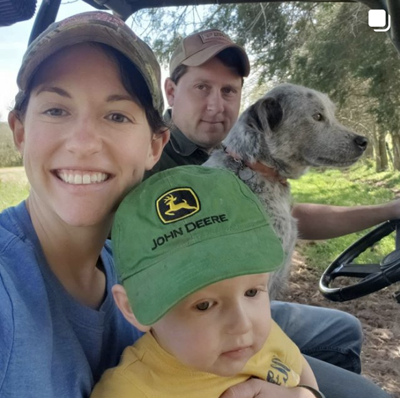 Woman, child with John Deer hat, dad, and dog...driving a tractor